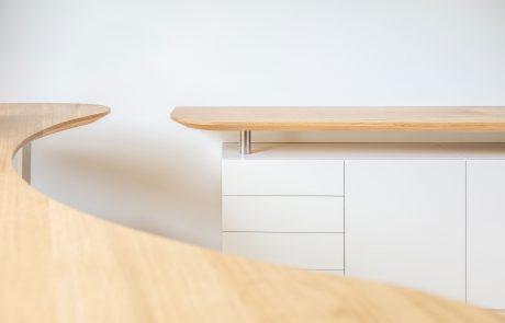 Schreibtisch mit geschwungener Tischplatte aus Holz mit passendem Sideboard