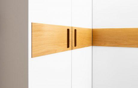 Schlanke Schrankwand mit praktischen Stauraum in weiß mit Glas und Holzgriffen aus Eiche im Detail