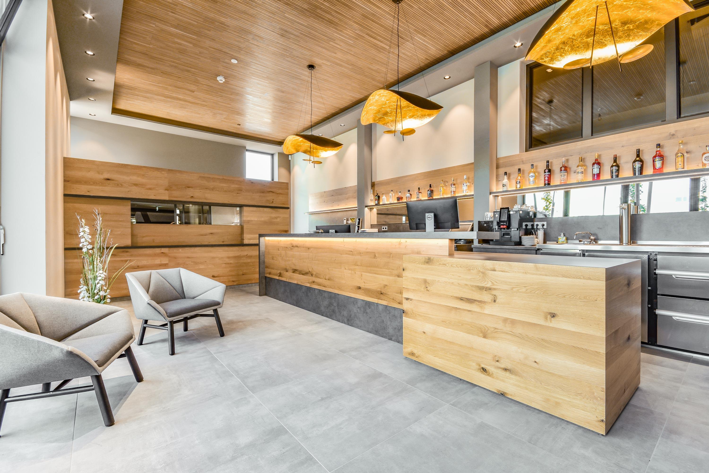 Empfang und Theke im Loft Hotel Heuboden aus Eichenholz mit goldenen Lampen